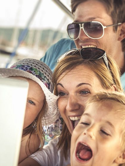 Happy family take a selfie on tablet with sons on a luxury yacht during summer vacations.
